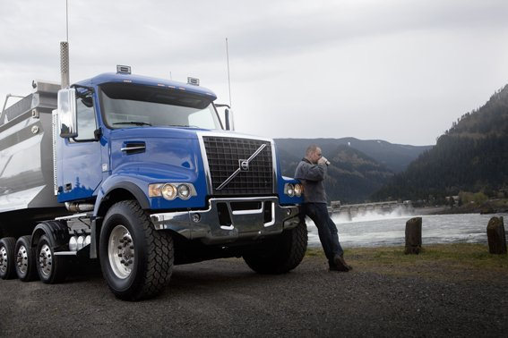 Blue Volvo VHD Truck with Driver and Mountains